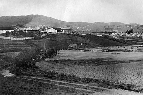 "Islais Creek (after being filled), 1918 Islais Creek (after being filled; see a small amount of water near bottom left). See ""History of Islais Creek"", ""Rivers in San Francisco in the Late 1800s,"" and ""Vanished Waters of Southeastern San Francisco."" Near Geneva Car Barn (center), Mount Davidson on left. There is an artichoke patch behind the old car barn at San Jose and Geneva. The tree line runs along Ridgewood Ave. (formerly known as Hamburg; changed during World War II). Photograph provided compliments of Ken and Kathy Hoegger, residents of Westwood Highlands. — Photo scanned, 2003, from copy made by Gregory Gaar in 1970s"